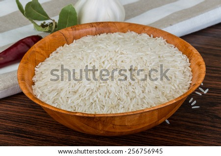 Raw Basmati rice in the bowl on wooden background - stock photo