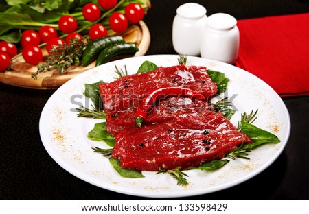 Raw beaf with vegetables served on plate - stock photo
