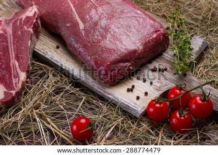 Raw beef and T-bone with tomatoes on a wooden board and hay. - stock photo
