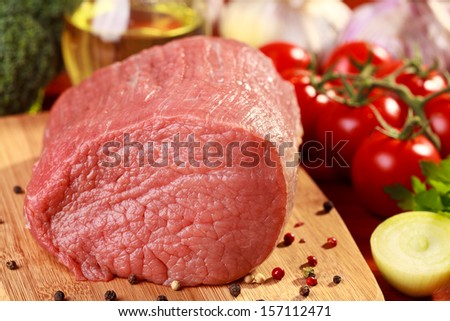 Raw beef and vegetables on wooden board - stock photo