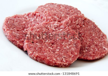 Raw beef burgers against white background - stock photo