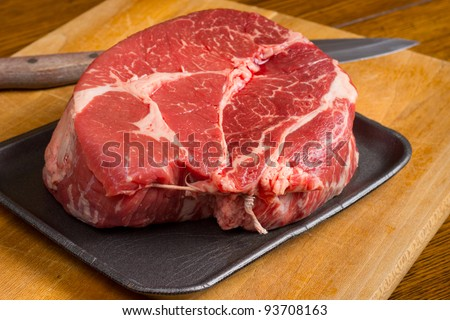 Raw beef chuck roast on a cutting board with knife