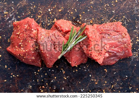 Raw beef cubes with rosemary and beefsteak spices on brown rustic background - stock photo