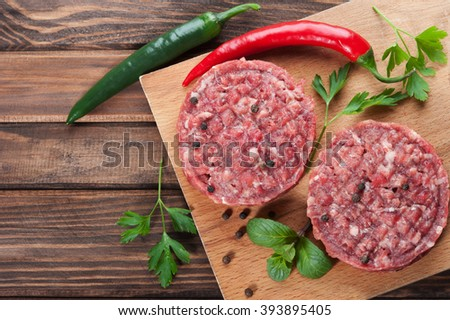 Raw beef cutlets with spices, rustic dark wooden background - stock photo