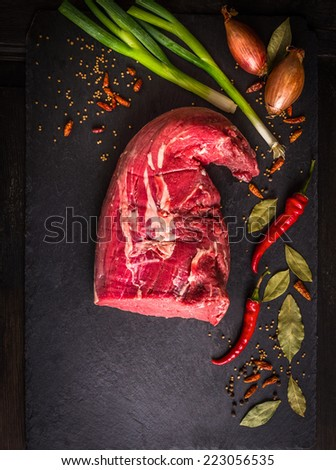 Raw beef fillet on dark background with spices : Bay leaf, pepper, chili, green onion, top view - stock photo