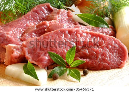 raw beef fillet on wooden board, fresh fillet chops with vegetables - stock photo