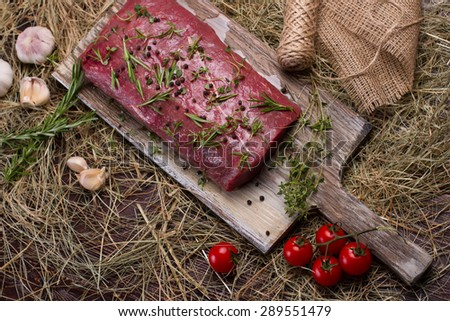 Raw beef marinated in spices. Meat on a cutting board. - stock photo