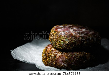 raw beef meat burger steak cutlets beefsteack on paper on dark wooden background. with copy space.