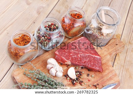 raw beef meat fillet with peppercorn and thyme and different spices in glass bottles ready to grill on wood figured aged board over table - stock photo