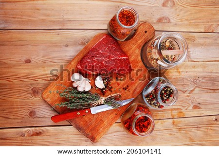 raw beef meat fillet with peppercorn and thyme and differnt spices in glass bottles ready to grill on wood figured aged board over table - stock photo