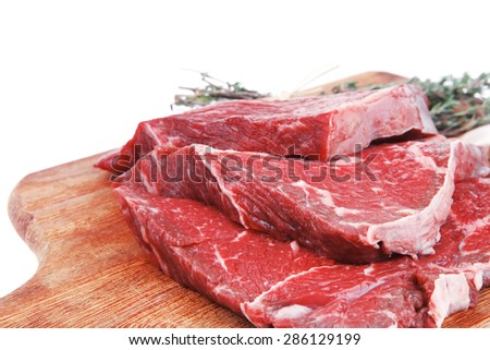 raw beef meat fillet with peppercorn and thyme ready to grill on wood figured aged board isolated over white background - stock photo