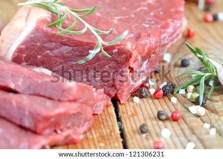 Raw beef meat with spice on wooden table - stock photo