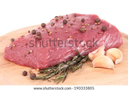 Raw beef meat with spices on wooden cutting board close up