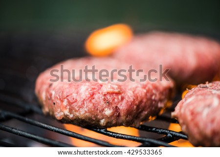 Raw beef on bbq grill with flames under