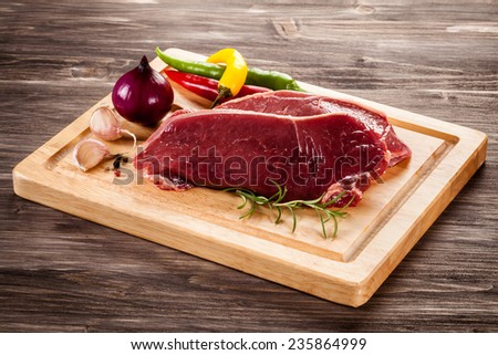 Raw beef on cutting board and vegetables - stock photo