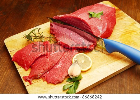 Raw beef on wooden board - stock photo