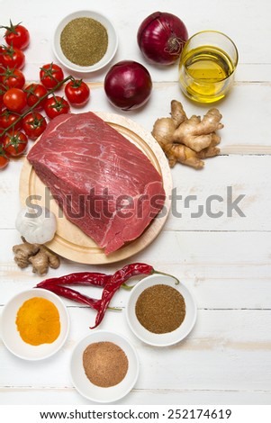Raw beef, onion, ginger, tomatoes, garlic, olive oil, chilli and spices - stock photo