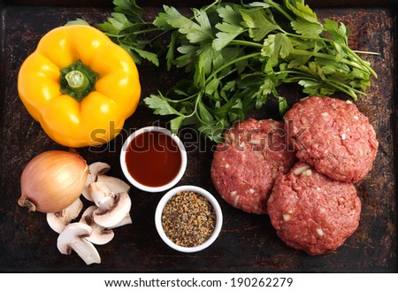 Raw beef patties with vegetables, barbecue sauce and spices - stock photo