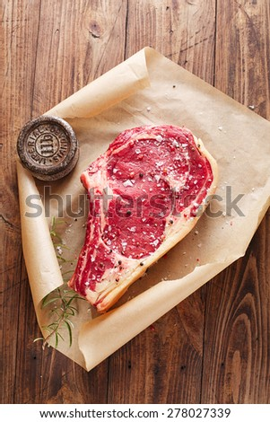 raw beef Rib bone  steak  on paper  and table with 2lb iron weight - stock photo