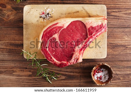 raw beef Rib bone steak on wooden board and table with spices - stock photo