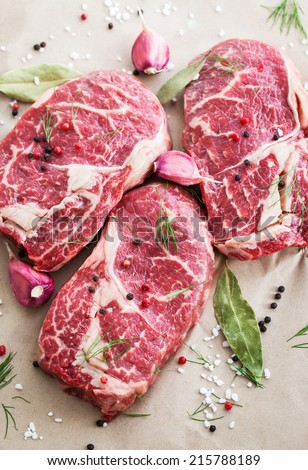 Raw beef ribeye steak on a baking paper, ready to cook - stock photo