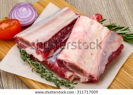 Raw beef ribs with rosemary and thyme - ready for cooking - stock photo