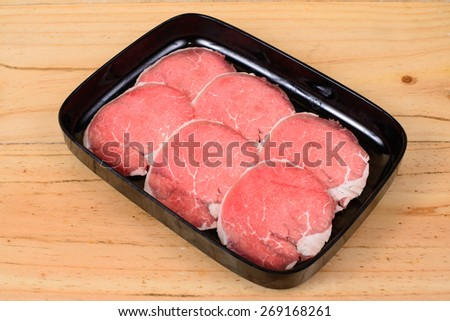 Raw beef sirloin tip in black tray on wooden background. - stock photo