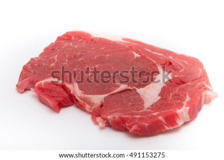 Raw beef steak on a white plate.