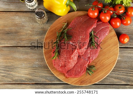 Raw beef steak on cutting board with vegetables and spices on wooden background - stock photo