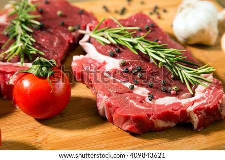 Raw beef steak on  wooden table with vegetables