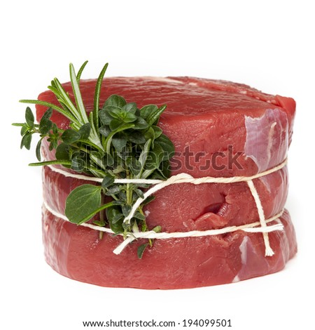 Raw beef steak tied with fresh herbs, isolated on white. - stock photo