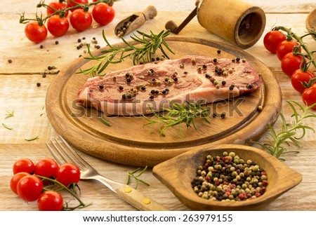 raw beef steak with herbs and spices on a wooden table - stock photo