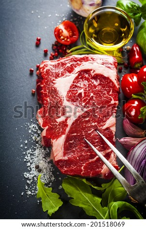 Raw beef steak with meat fork and ingredients on a dark slate background - stock photo
