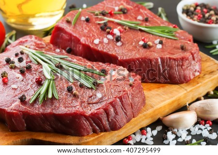 Raw beef steak with spices and ingredients for cooking on cutting borard and  slate background. Top view. - stock photo