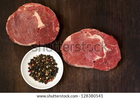 Raw beef steaks and peppercorns on wooden board.  Overhead view. - stock photo