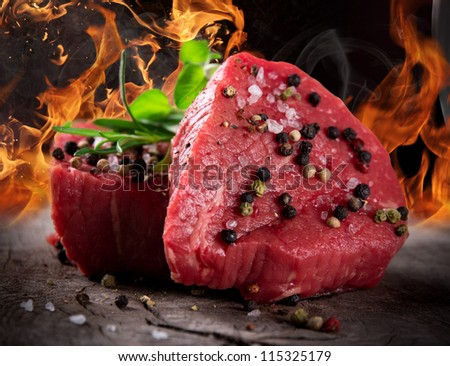 Raw beef steaks with fire flames - stock photo