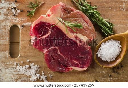 Raw beef t-bone steak on a old wooden board. - stock photo