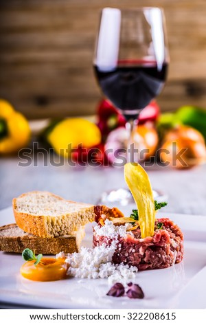 Raw beef .Tasty Steak tartare. Classic steak tartare on white plate with egg bread and cup red wine  - stock photo