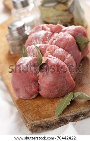 Raw beef with bay leaf ready to roast - stock photo
