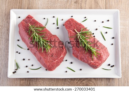 Raw beef with rosemary and pepper - stock photo