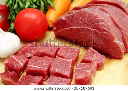 Raw beef with vegetables on wooden plate  - stock photo