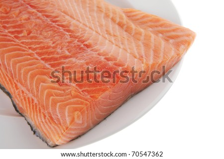 raw big salmon bar on white plate isolated over white background . shallow dof