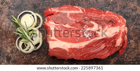 Raw blade roast with onions and rosemary on brown rustic background