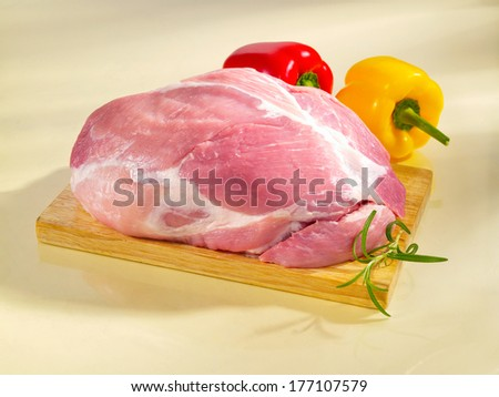 Raw boneless shoulder square cut on a cutting board and yellow background. - stock photo