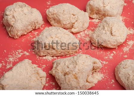 Raw breaded boneless wings on red surface - stock photo