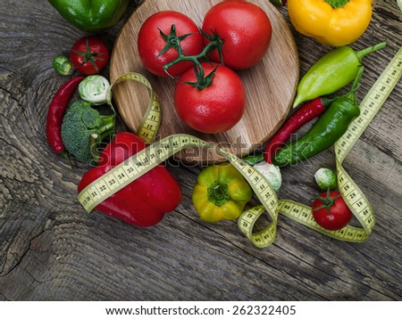 Raw broccoli, tomatoes, peppers with measuring tape on wooden table - stock photo