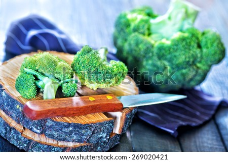raw brocoli and knife on the wooden background - stock photo