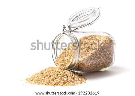 Raw brown rice and jar isolated on white. - stock photo
