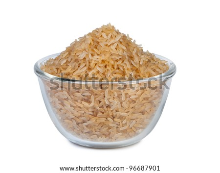 Raw brown rice in glass bowl on white background. - stock photo