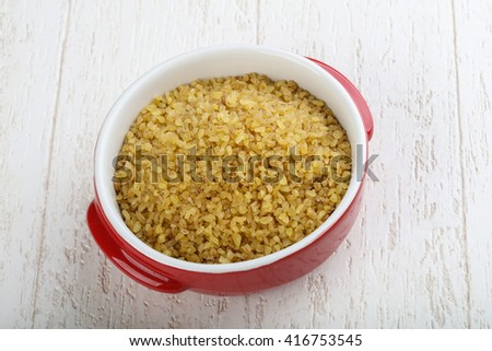 Raw bulgur in the bowl ready for cooking